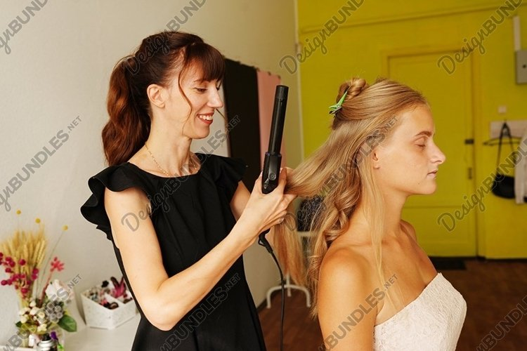 Beautiful young hairdresser giving a new haircut to woman example image 1