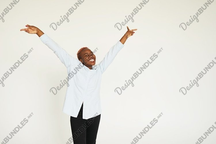 Energetic glad woman with dark skin raising her hands example image 1