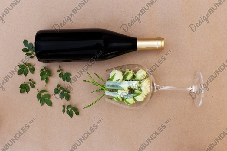 Wineglasses with fresh white roses and a bottle