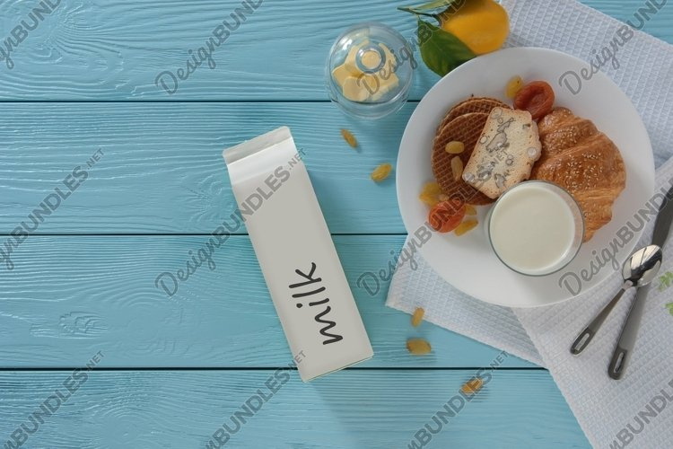 Milk in carton box and baking on blue wooden background example image 1