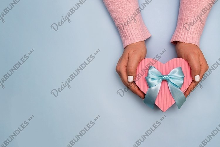 Heart shape gift box in female hands with copy space example image 1