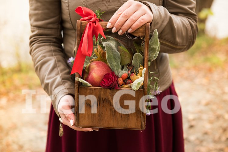 Beautiful girl holding a basket of flowers and autumn harves