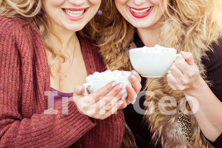 Two smiling women are sitting outside with cups