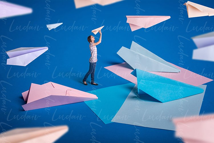 Surreal design. Young girl let paper airplanes. example image 1