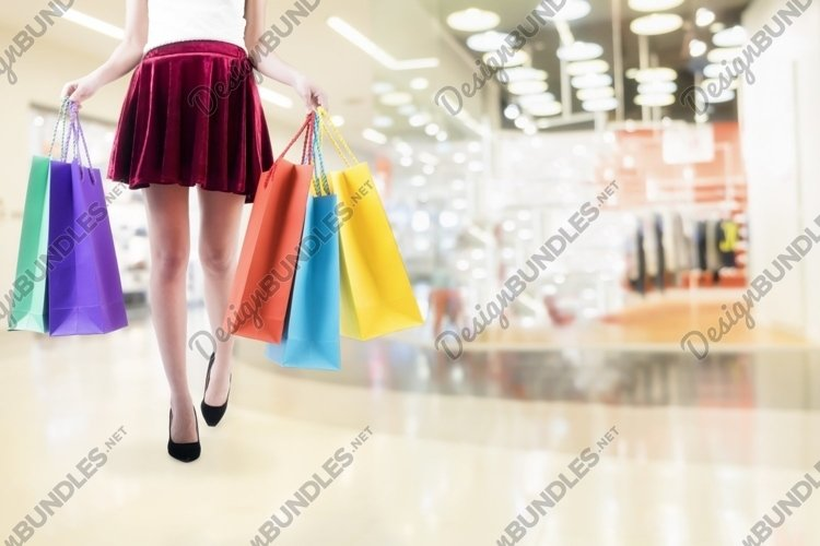 Woman shopping in shopping mall and carrying shopping bags. example image 1