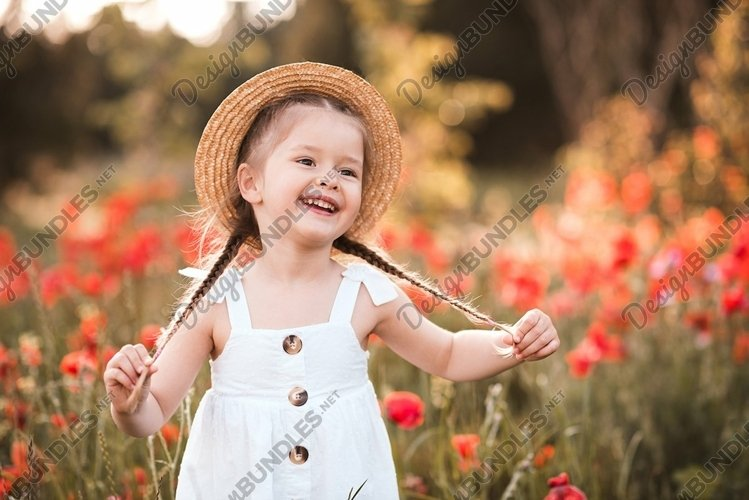 Happy child girl in meadow outdoors with flowers