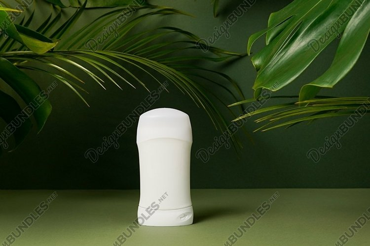 Deodorant or antiperspirant on green leaves background