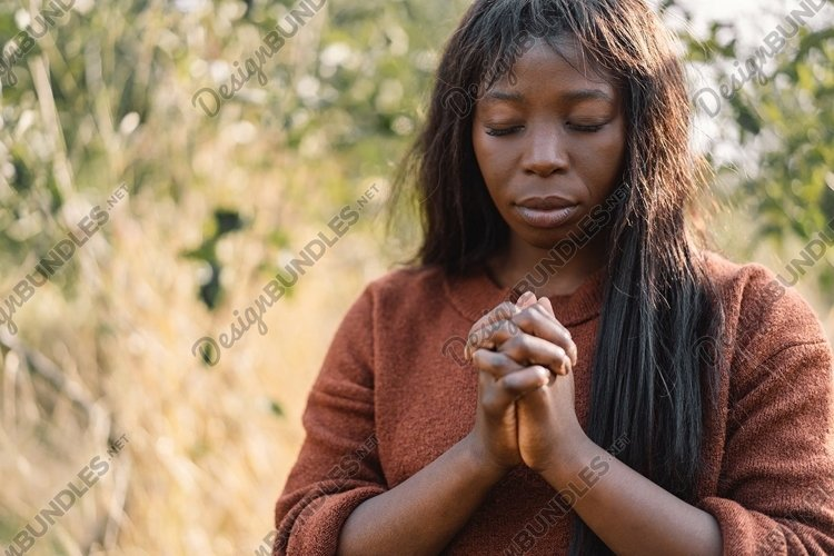 Afro girl closed her eyes while praying outdoors example image 1