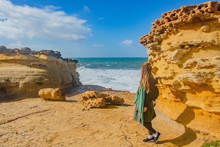 Woman dreamily looks at the Atlantic ocean.