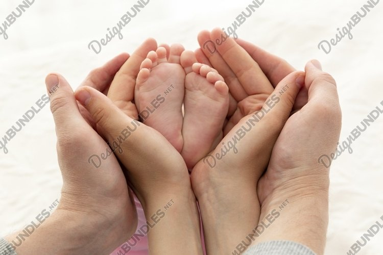 Happy parents hold their newborn baby's feet example image 1