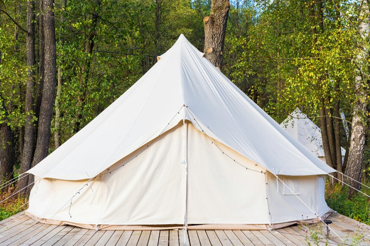 White canvas glamping bell tent at forest