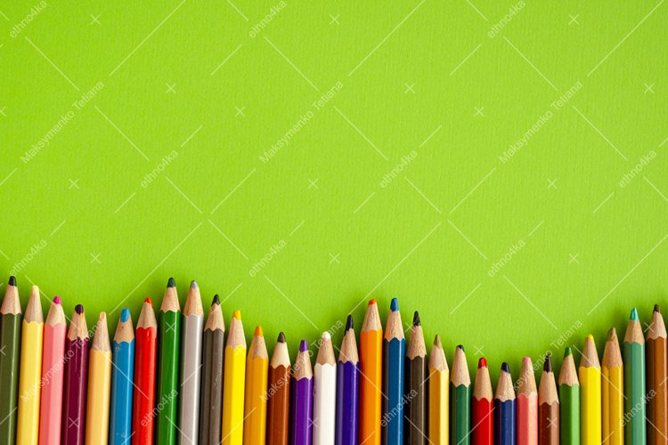 Set of decorative frames with crayons on green background.