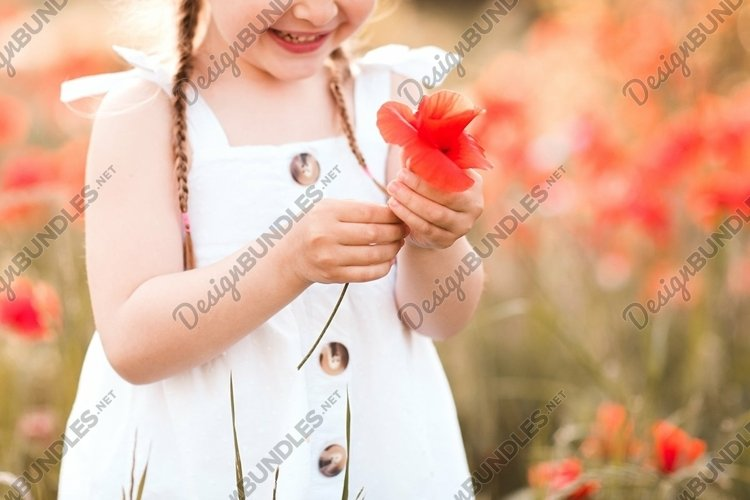 Cute child girl with flowers in field outdoors