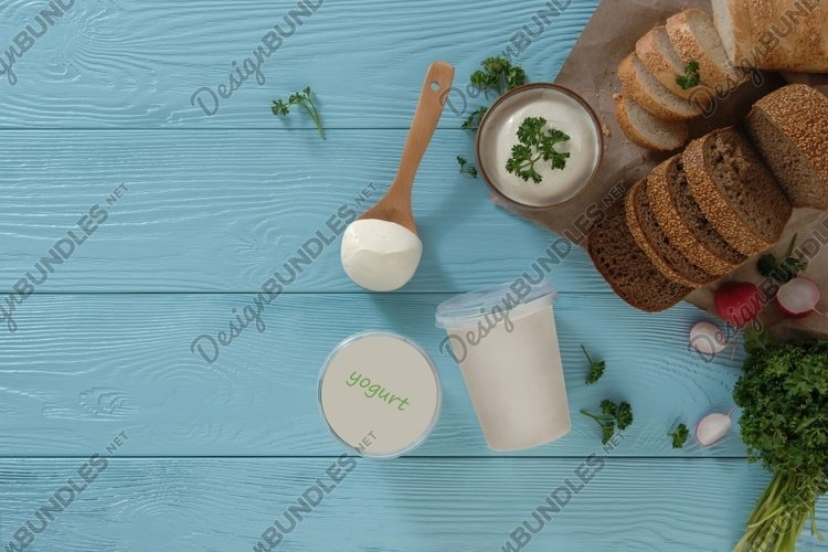Yogurt in a plastic container and bread on a blue background example image 1