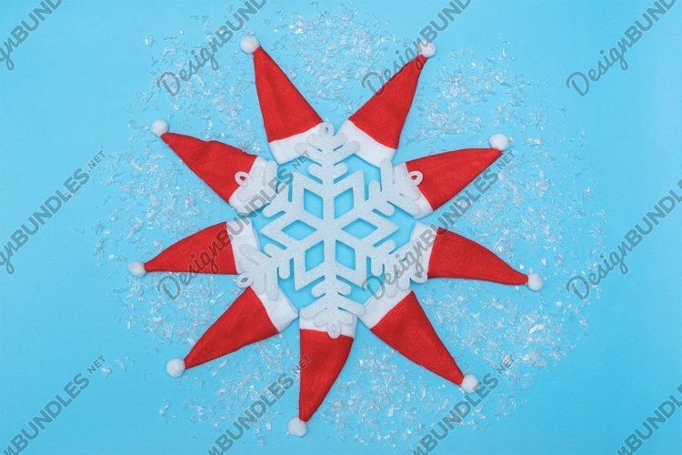 Christmas hats and snowflake on pastel blue background. example image 1