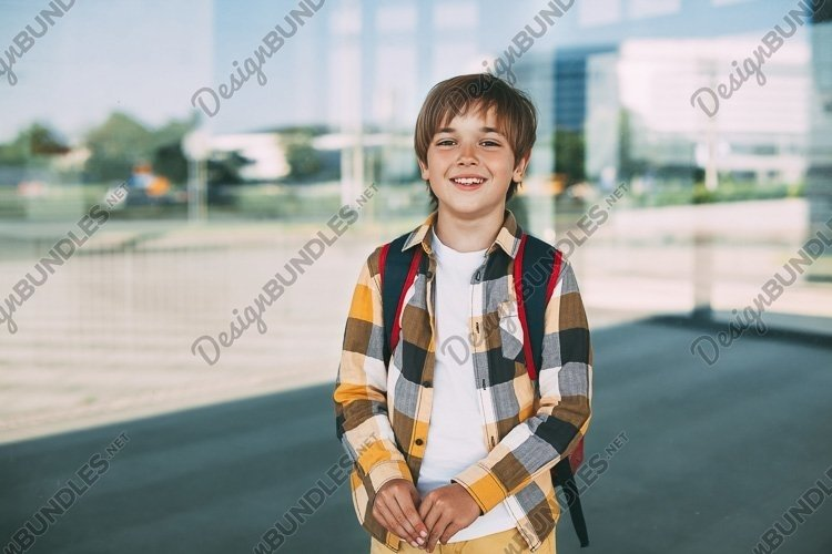 Happy boy with a backpack stands near the school and smiles example image 1