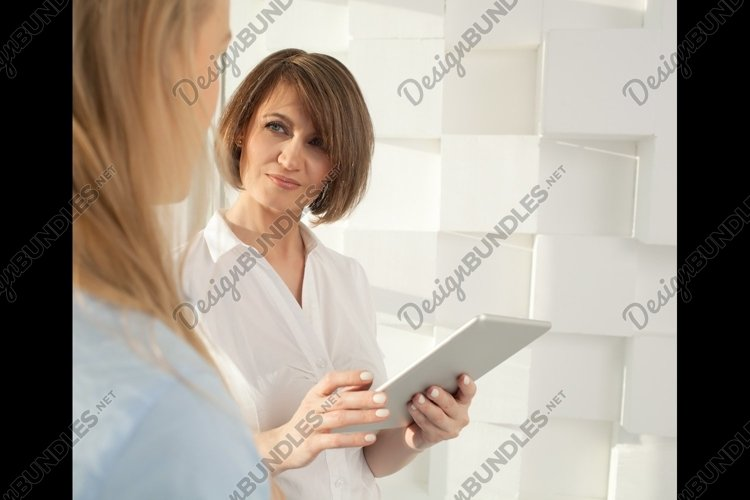 Portrait of brunette woman with tablet looking at her collea example image 1