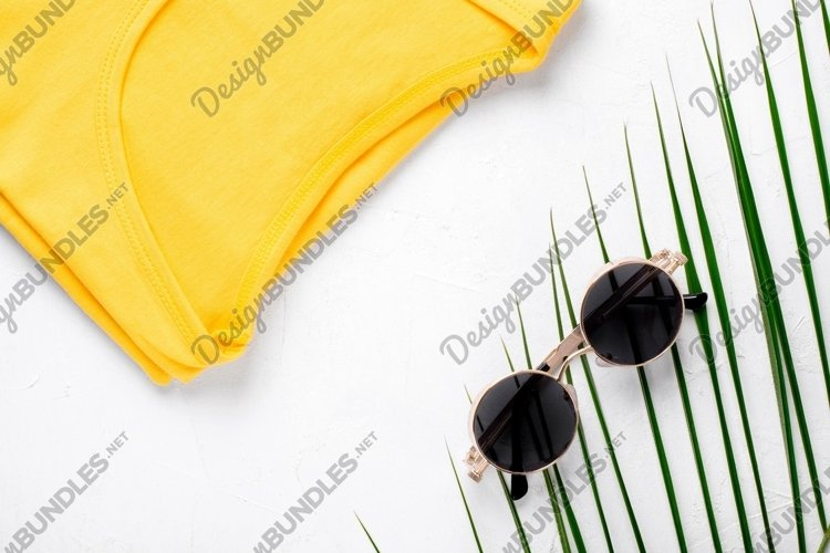 Summer fashion flat lay with T-shirt and sunglasses