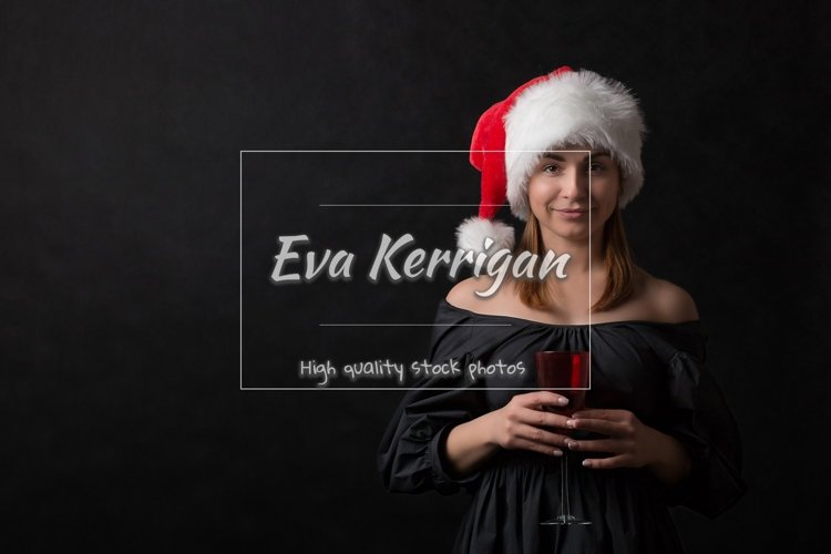 A girl in a santa hat raises a red glass with a toast. example image 1