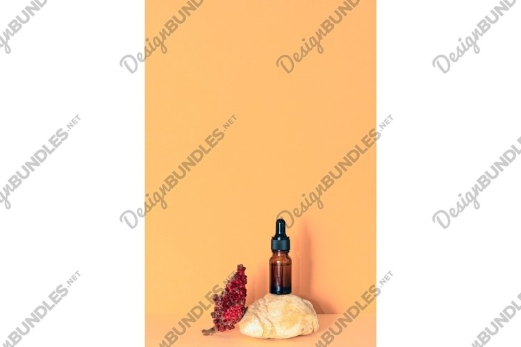 Glass cosmetic bottle with dropper standing on beige stone example image 1