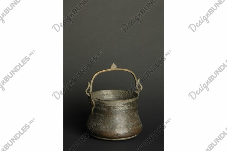 Ancient metal bowl on dark background. Bronze tableware example image 1