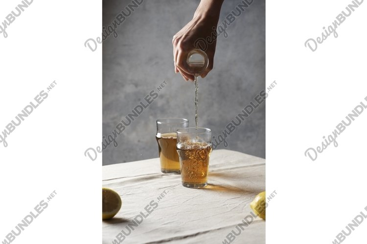 Woman pouring black hot tea in a glass example image 1