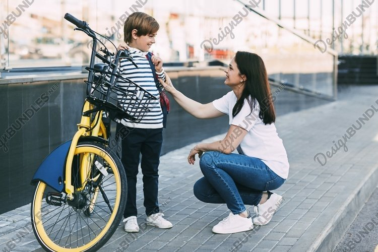 Mom takes her son to school on a bicycle example image 1