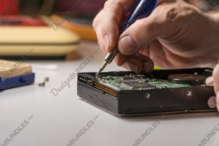 Electronic engineer repairs computer hard drive example image 1
