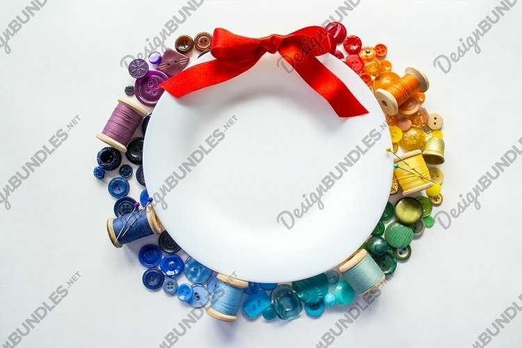 White plate, rainbow buttons, threads, wreath. Copy space