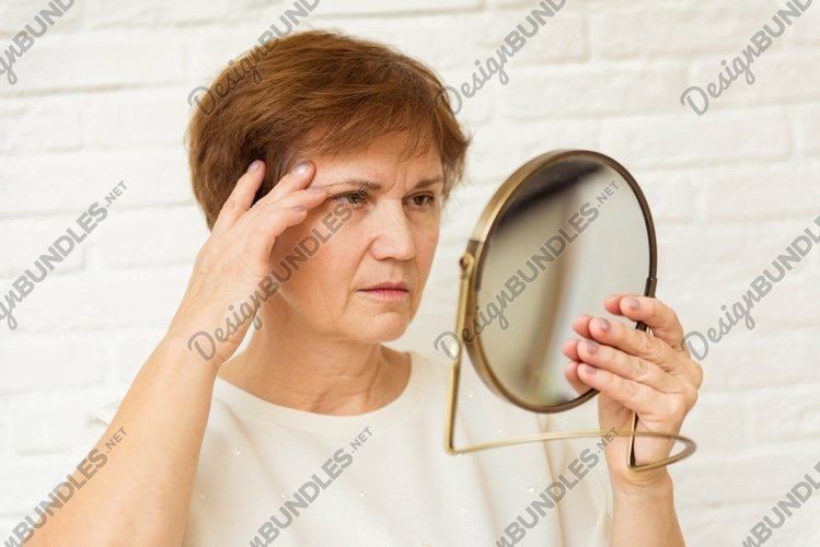 Unhappy aged woman looking in mirror at home example image 1