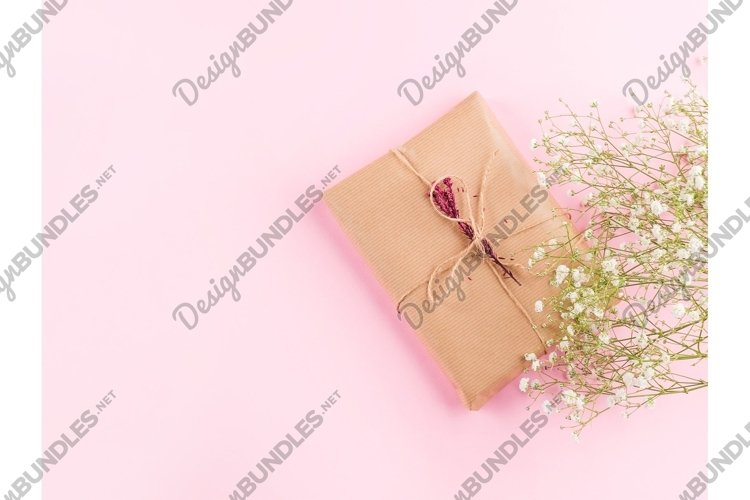 White flowers and wrapped gift box on pastel pink background