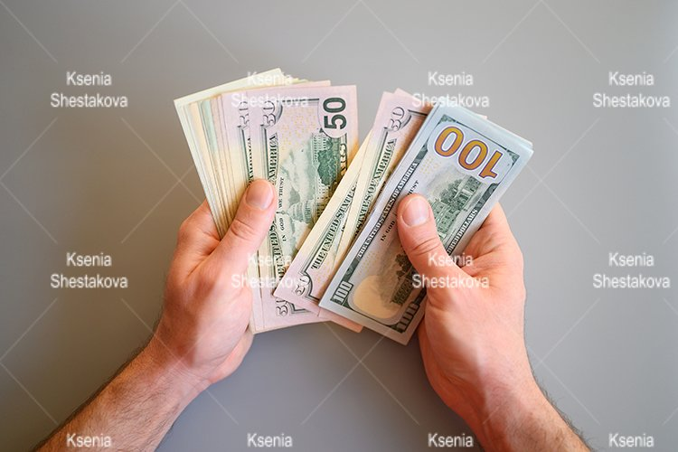 men's hands hold and count different American dollar bills example image 1