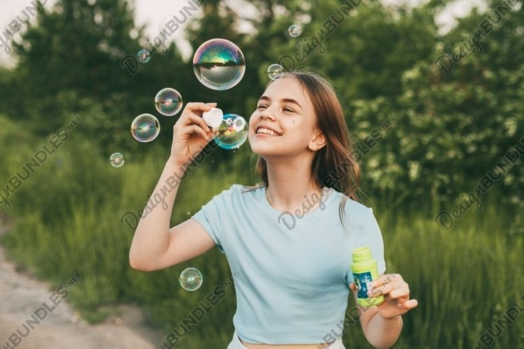 Lovely girl with a beautiful smile blows soap bubbles. example image 1
