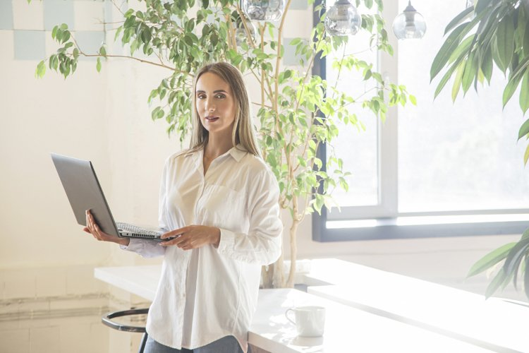 Beautiful caucasian girl holding a laptop in her hands. example image 1