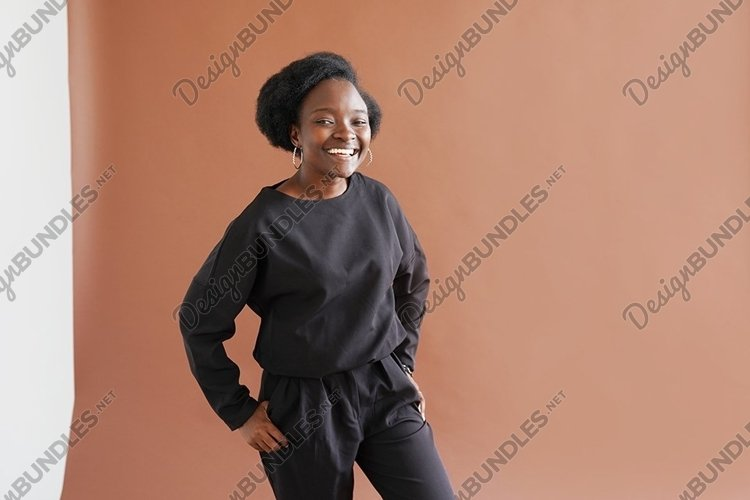 Smiling young african woman posing on brown background example image 1