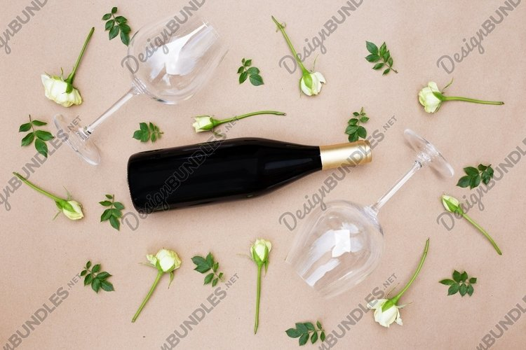 Empty wineglasses and a bottle with fresh white roses