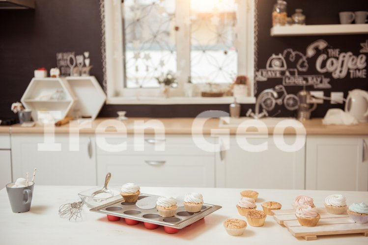 Preparation of brown cupcakes with white cream on the table