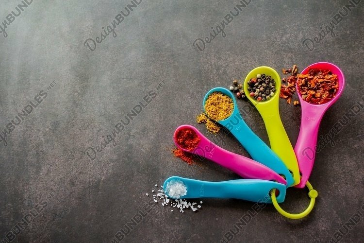 Multicolored measuring spoons with spices. Copy space example image 1