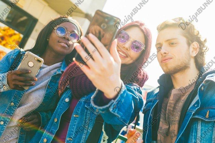 Multiracial friends taking selfie outdoors.
