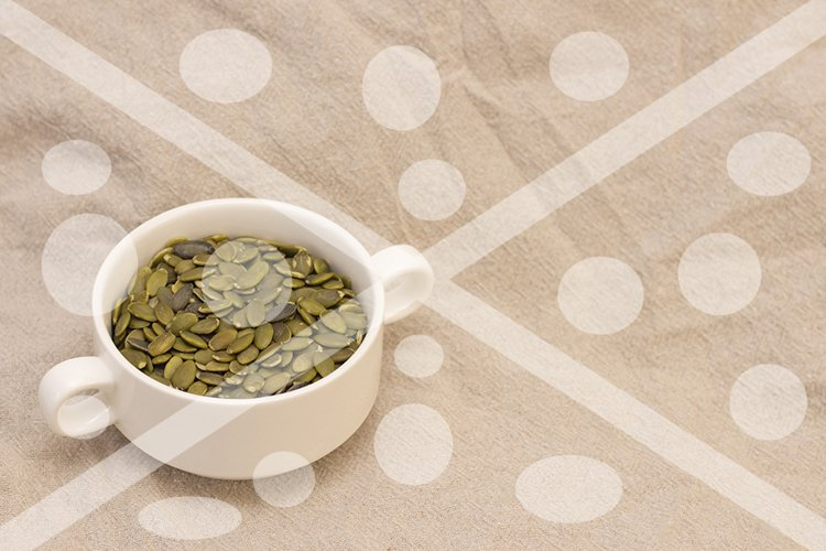 pumpkin seeds, in a white cup on natural linen. pumpkin seed example image 1