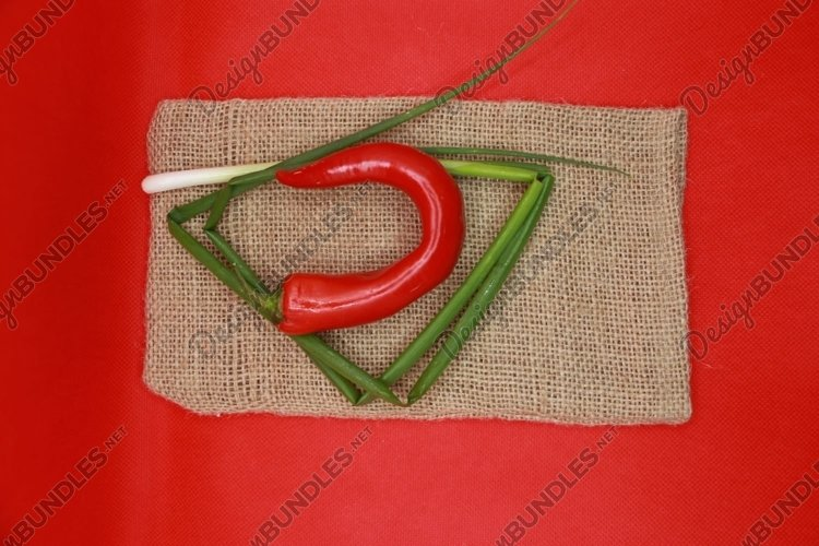pepper and green onions on a red background example image 1
