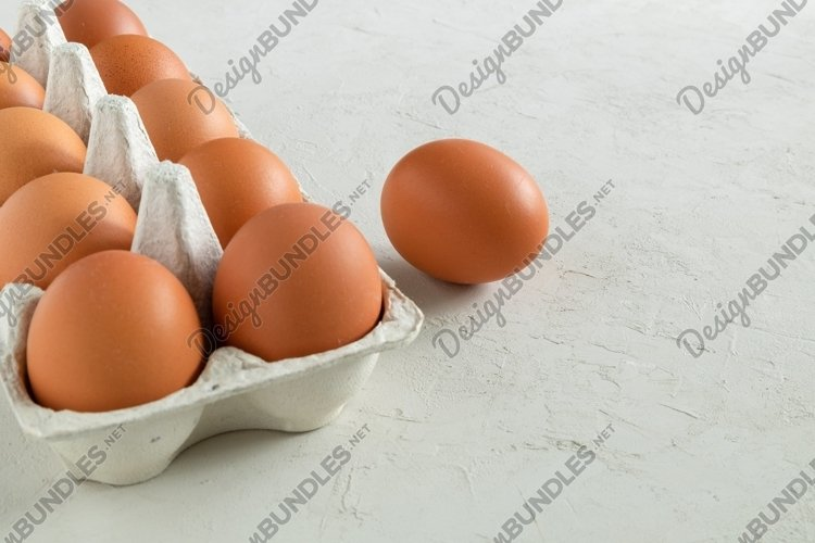 Close-up of chicken eggs in an egg carton. example image 1