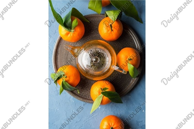 Winter tea in pot and tangerines on blue backgound example image 1