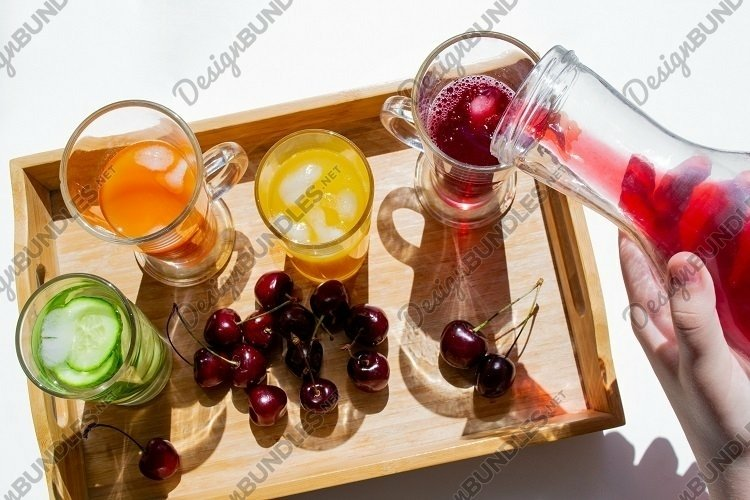 Colorful drinks, cherries. Decanter pours red juice, shadows example image 1
