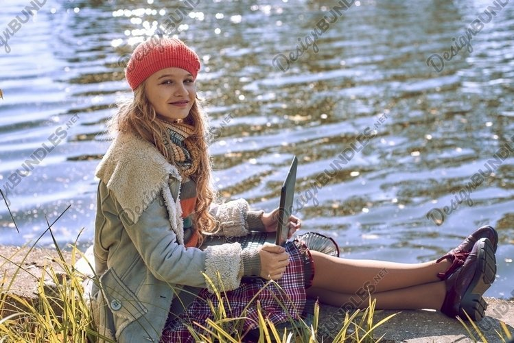 young girl in autumn with notebooks near the river