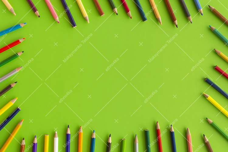 Decorative frame of colored pencils on green background.