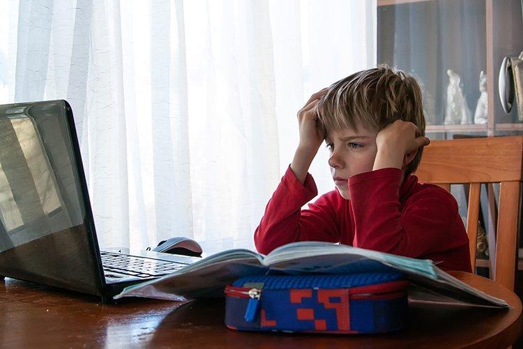School kid in self isolation using laptop for homework