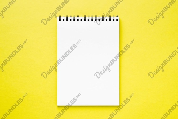 Blank notepad white page on yellow desk, color background