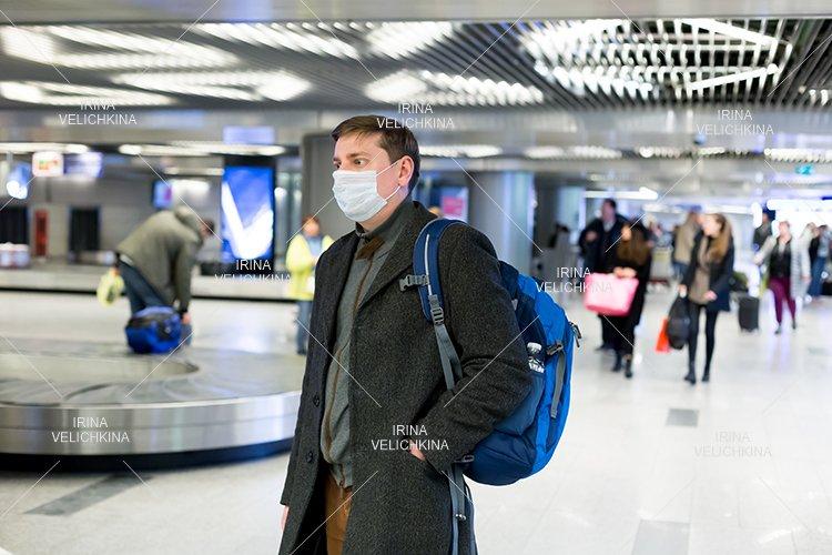 Man in face mask, coat in airport, coronavirus protection