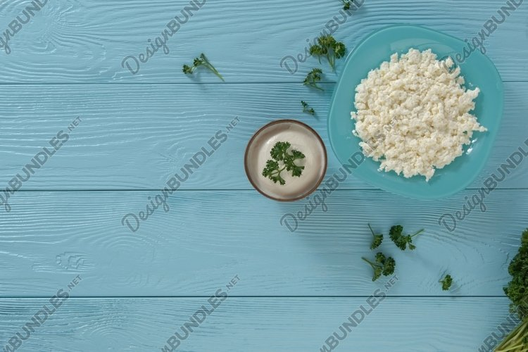 Cottage cheese in a plate and yogurt on a blue background example image 1